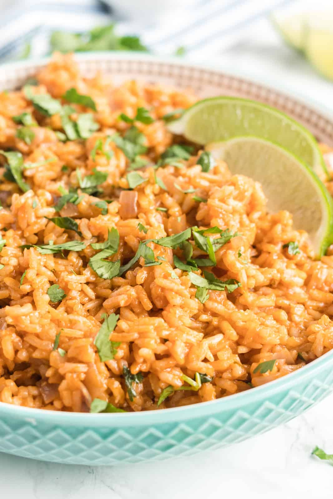 Rice in bowl topped with chopped cilantro and two lime wedges