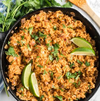 easy Spanish rice in cast iron skillet garnished with lime and cilantro