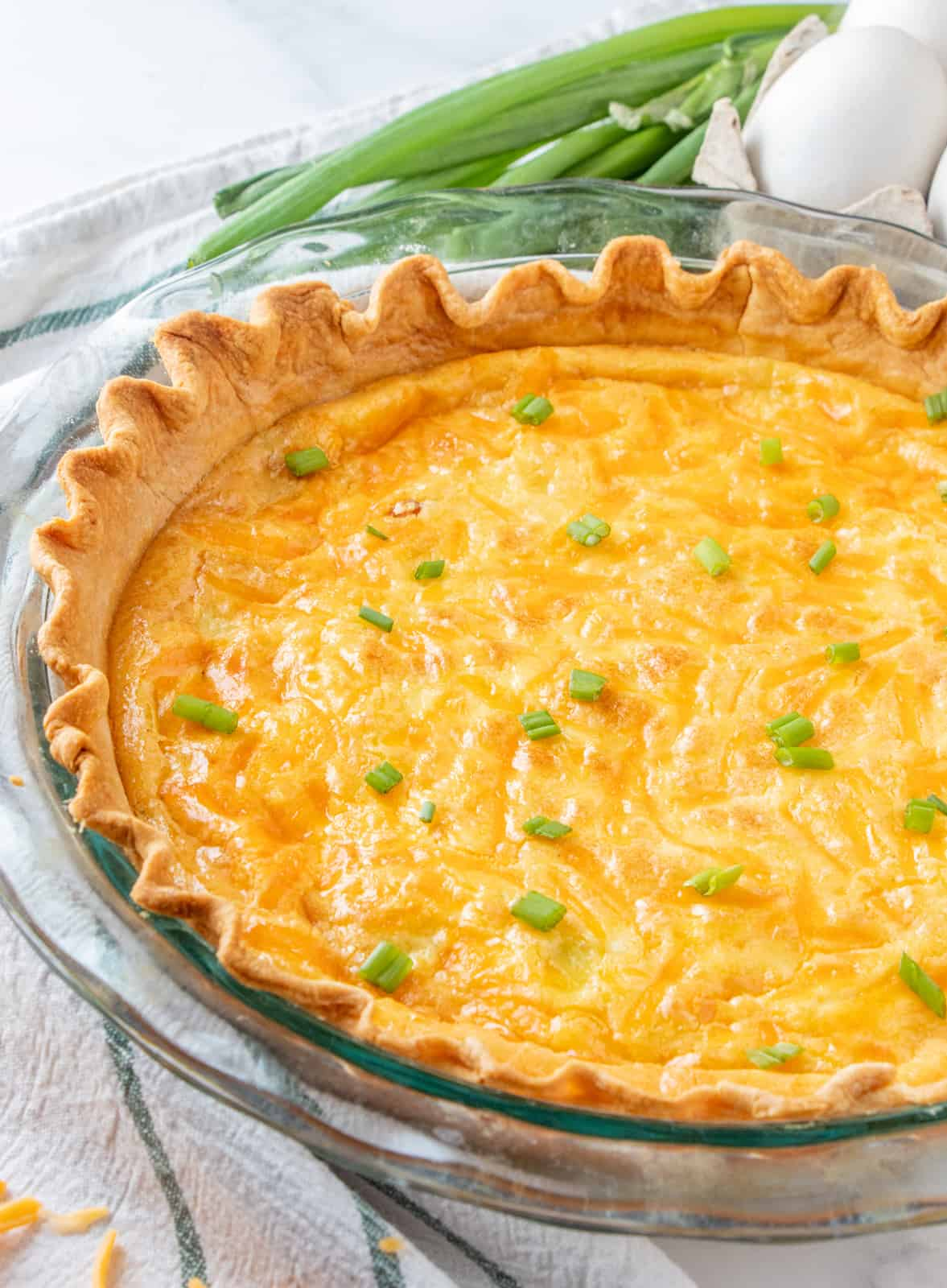 Baked Ham and Cheese Quiche in pie plate before cutting topped with green onions