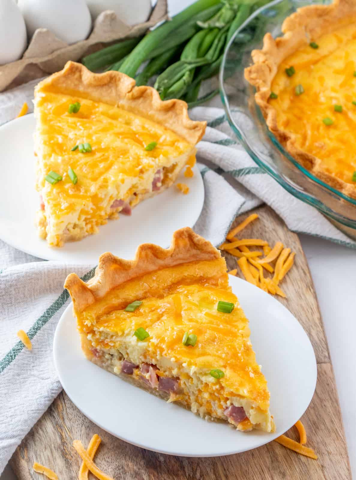 Quiche on two plates topped with green onions and garnished with cheese