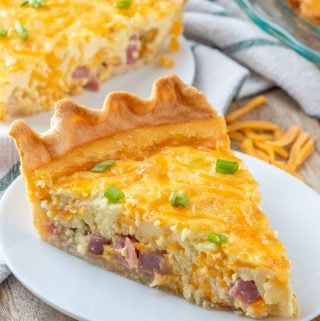 slice of quiche on white plate topped with green onions