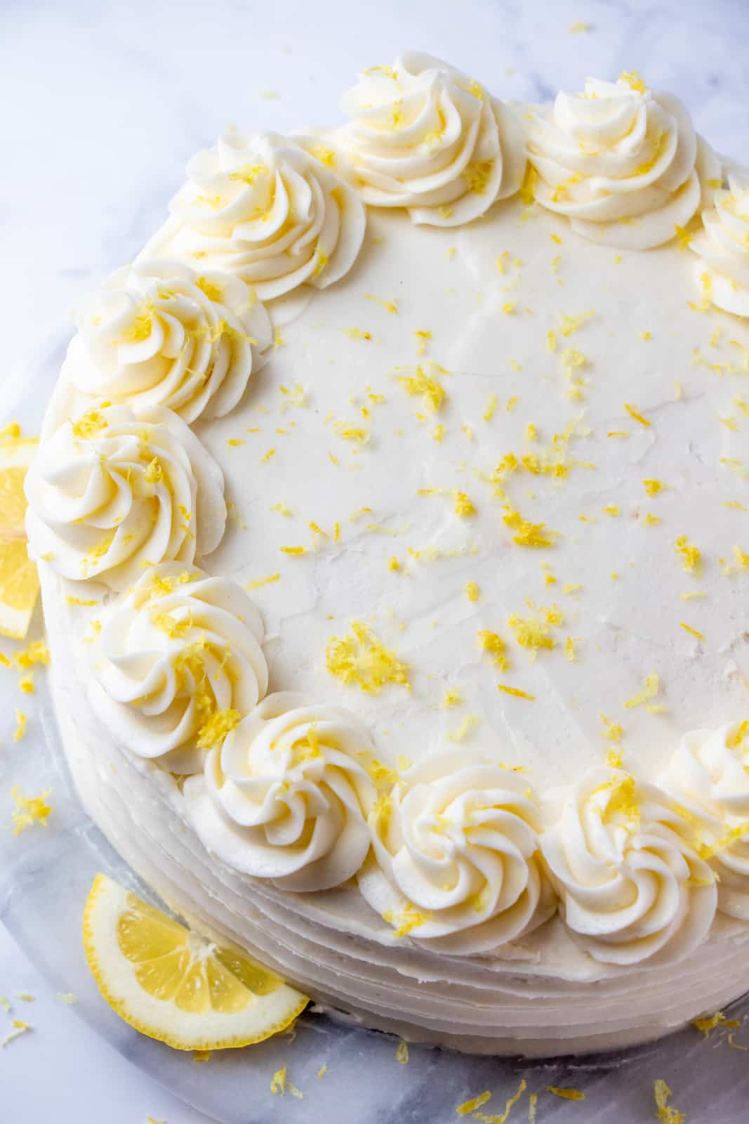Overhead photo showing top of cake with piped swirls and lemon zest decorations
