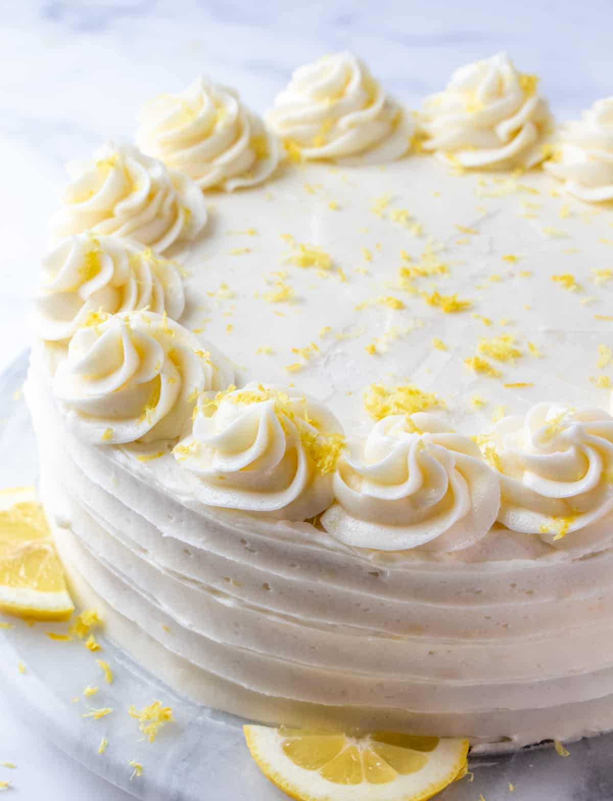 Decorated lemon layer cake on turntable with swirls, slices of lemon and lemon zest on top