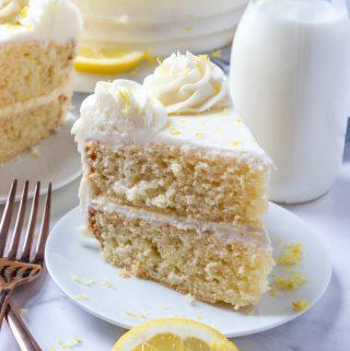 slice of lemon cake on white plate with forks and garnished with lemon zest
