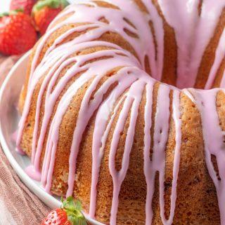 Photo of finished strawberry cake glazed on serving platter with strawberry garnish
