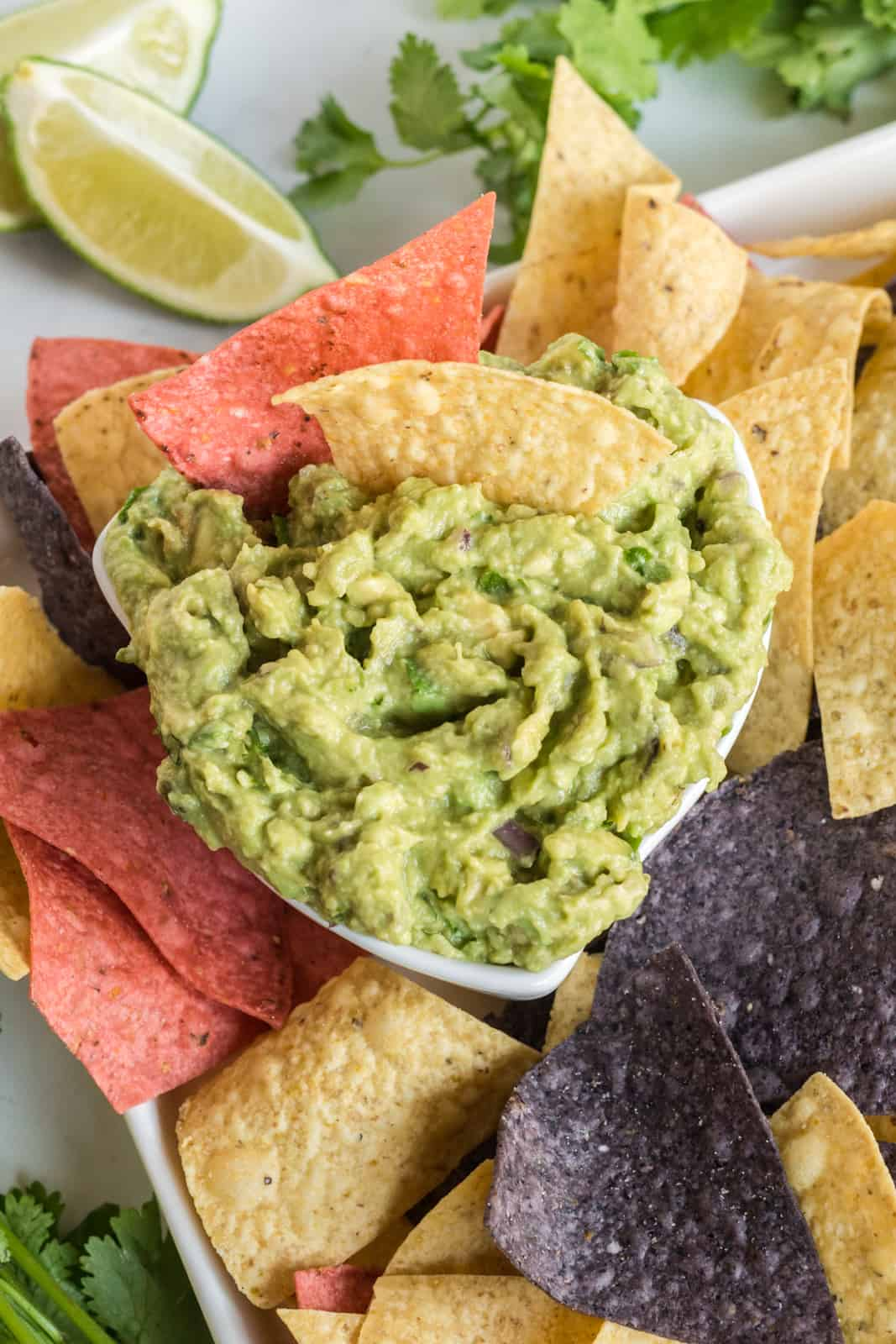 Overhead photo of guacamole in serving bowl surrounded by multicolor chips