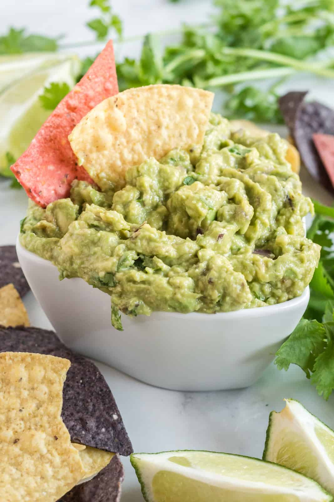 Easy Guacamole in white bowl with chips sticking out of it