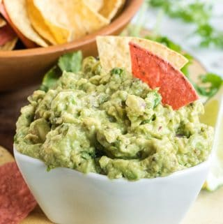 Guacamole in bowl with chips sticking out of it and bowl of chips in background
