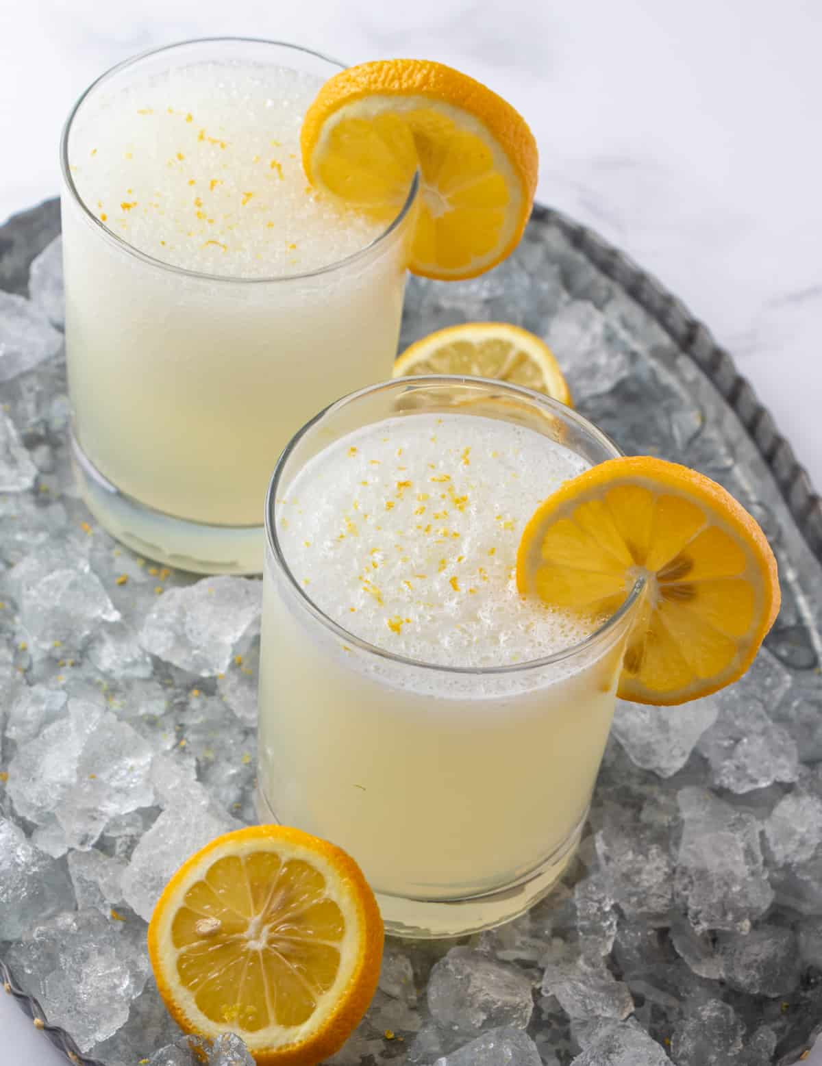 Frozen lemonade in two glasses surrounded by ice