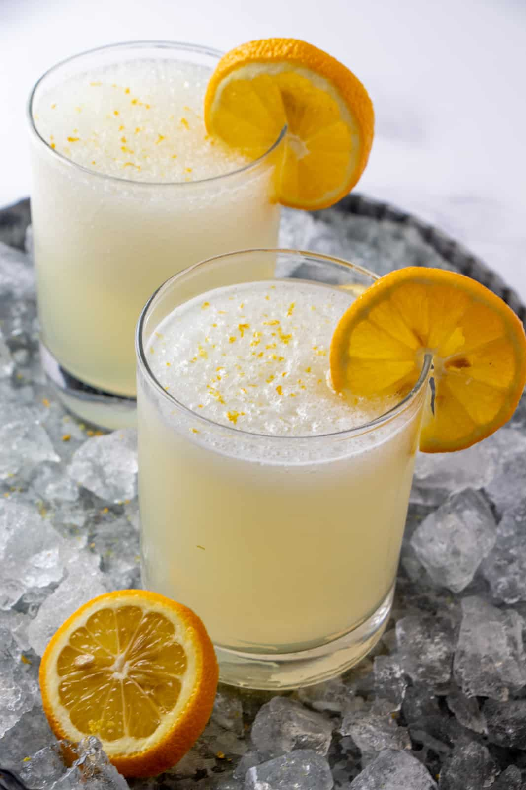 close up of two glasses of frozen lemonade garnished with lemon