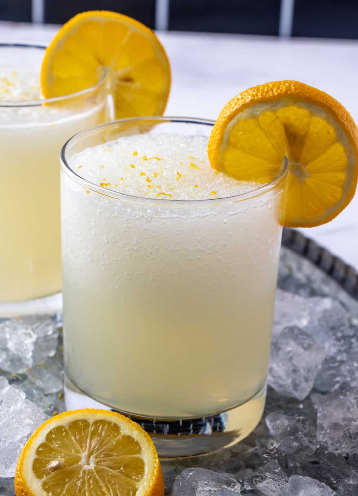 lemonade in glass surrounded by ice and garnished with lemon