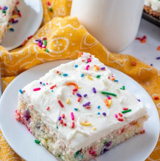 Slice of Funfetti Cake on white plate topped with sprinkles and milk in background