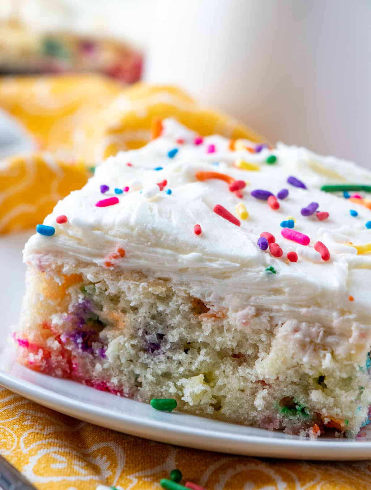 Up close side photo of cake on plate showing sprinkles in the cake