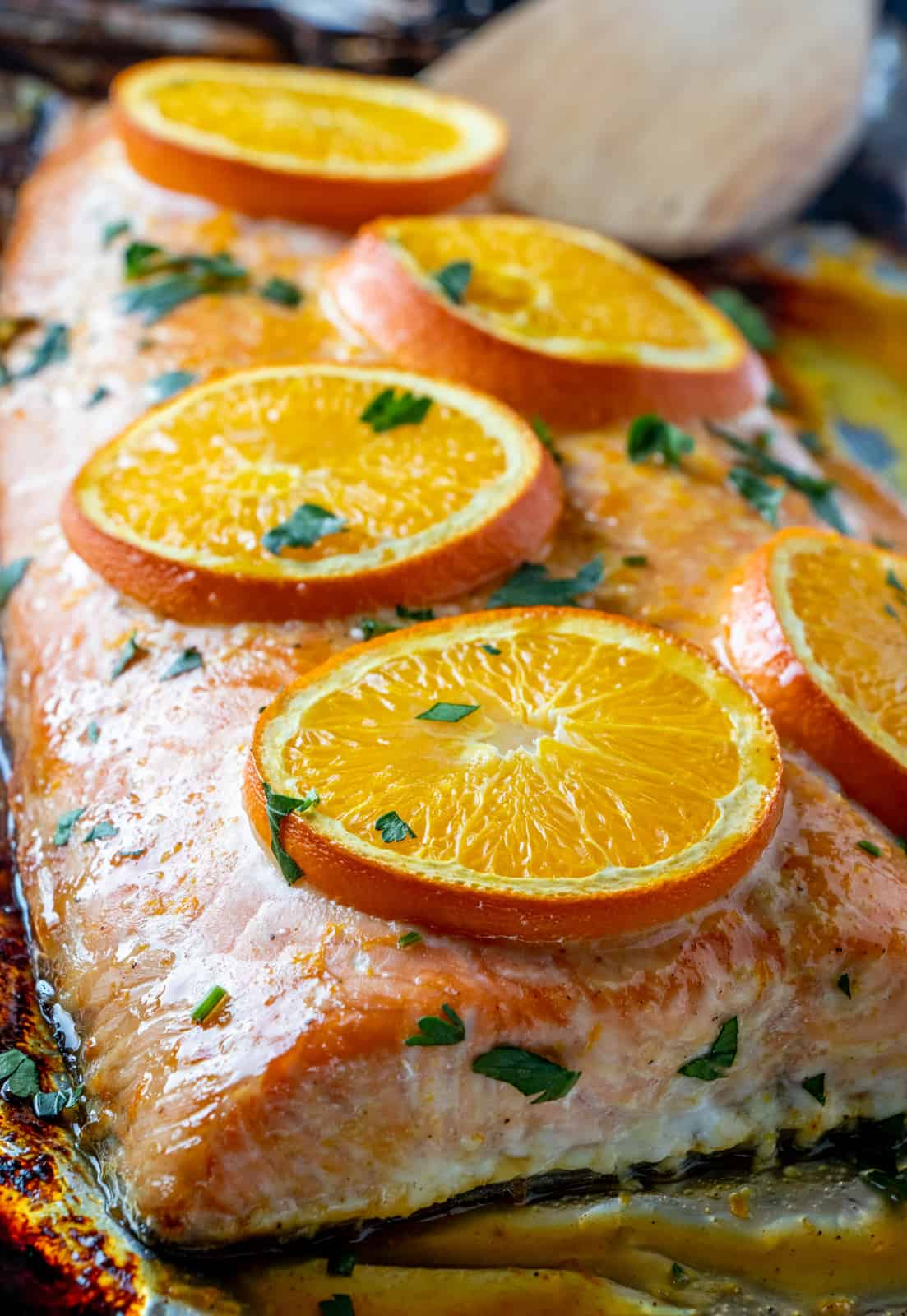 Close up photo of salmon on baking sheet topped with oranges
