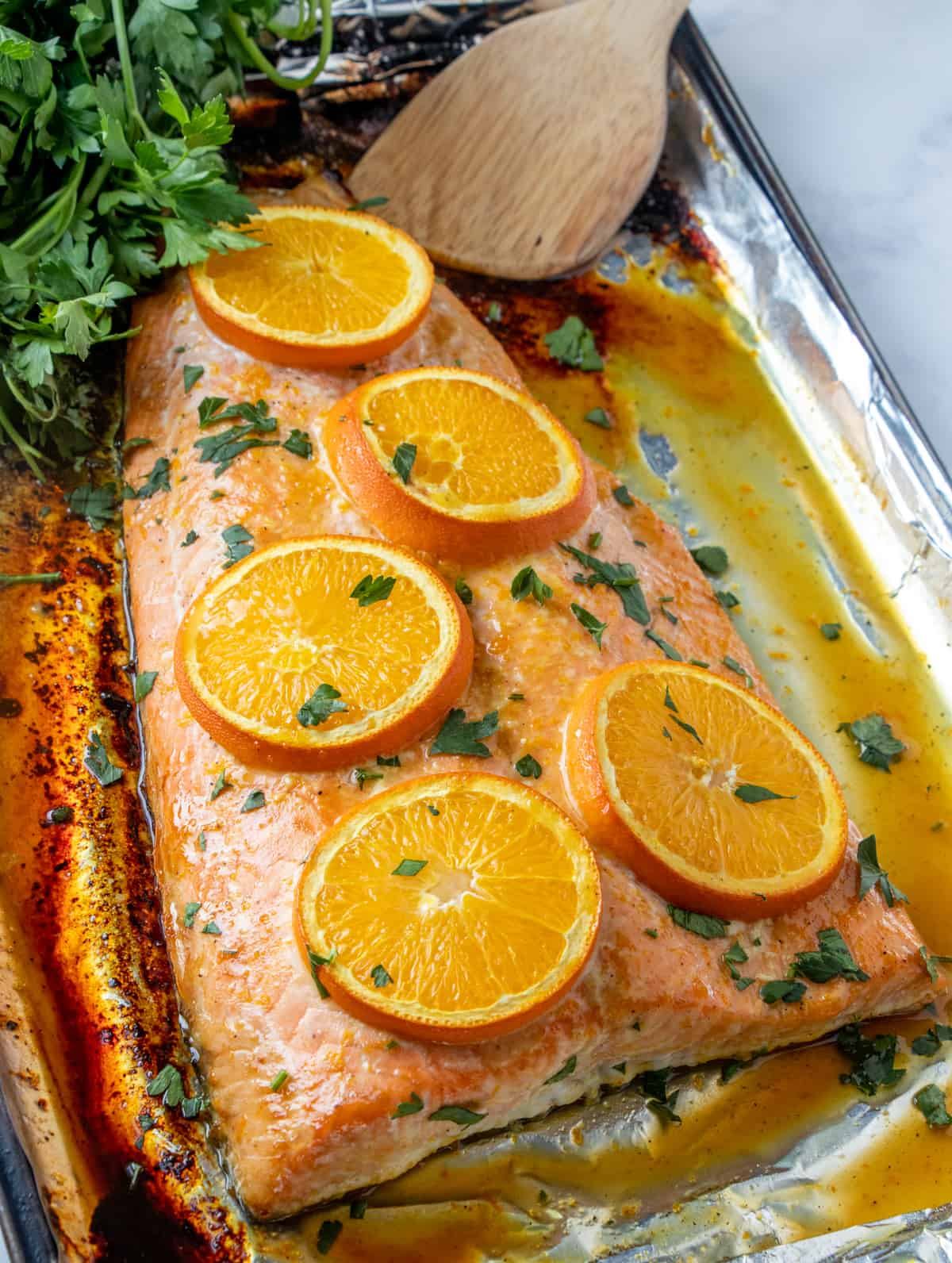Overhead photo of baked salmon on baking sheet topped with oranges