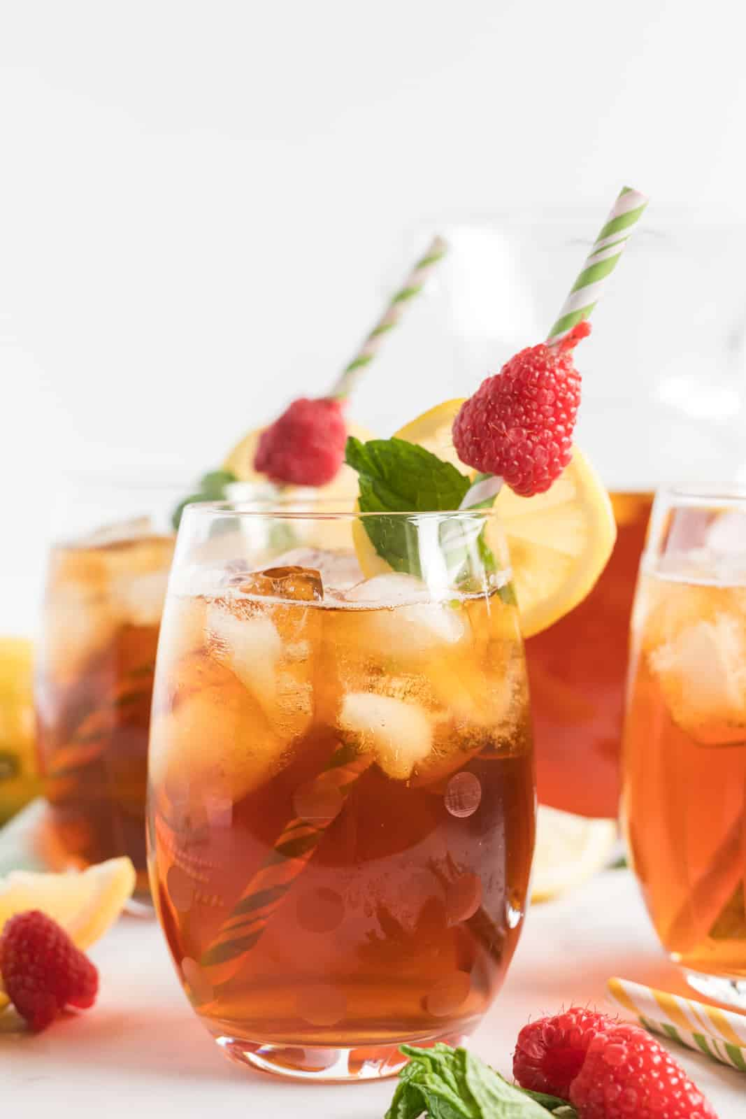 Tea in serving glasses garnished with mint leaves, raspberries and lemon