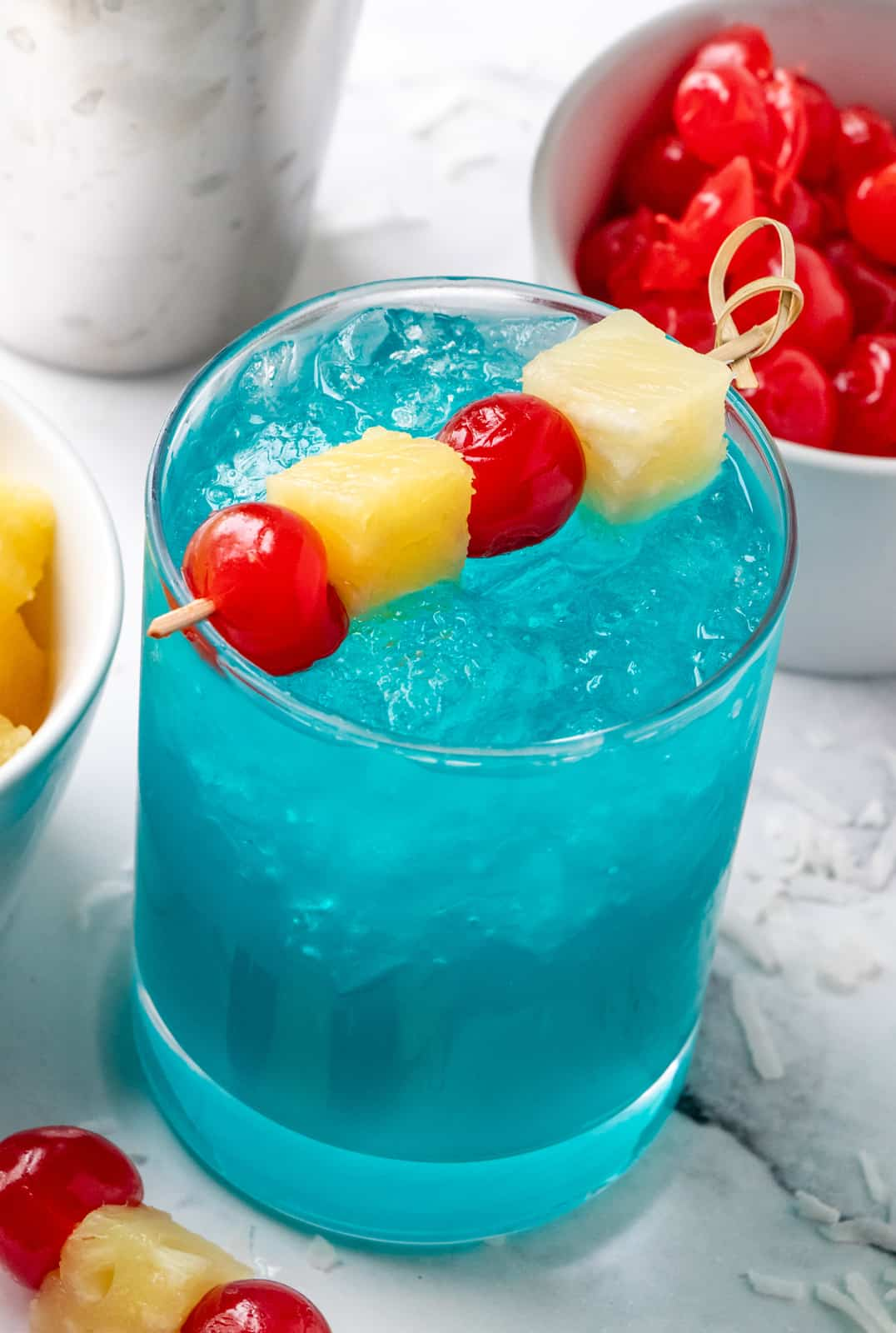 Close up of cocktail with a long skewer holding pineapple and cherries