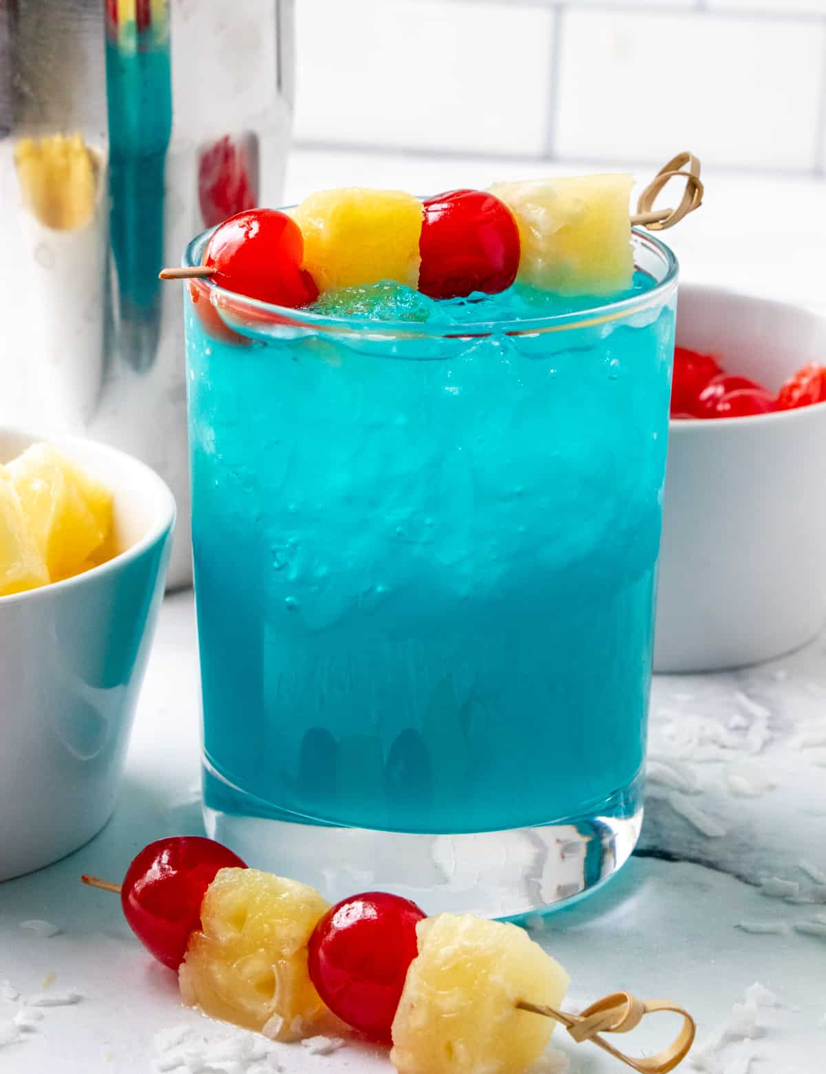 Straight on Hawaiian Cocktail surrounded by cherries and pineapple