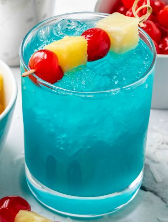 Blue Hawaiian Cocktail garnished with cherries and pineapple