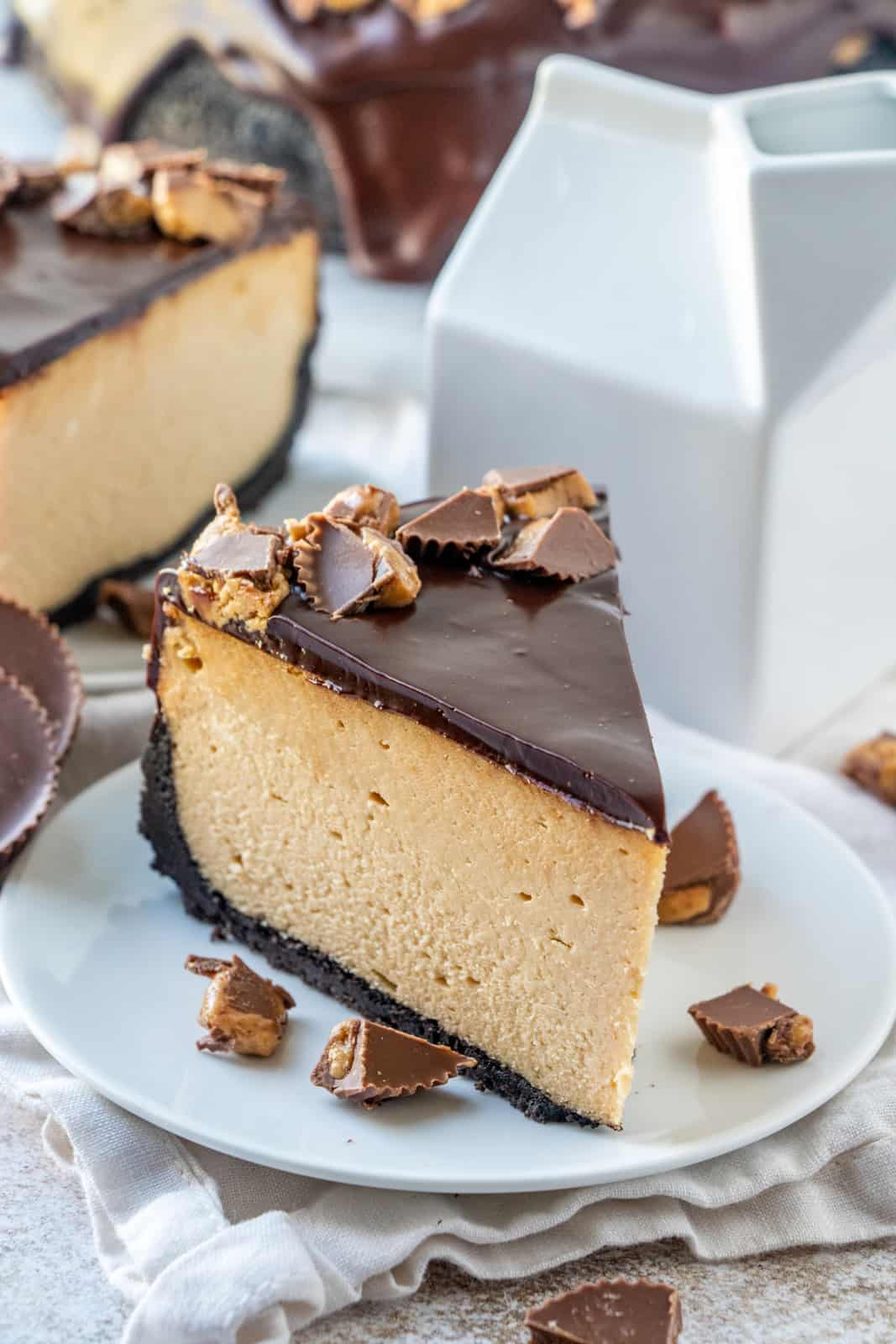 Slice of Peanut Butter Cheesecake on white plate surrounded by diced peanut butter cups