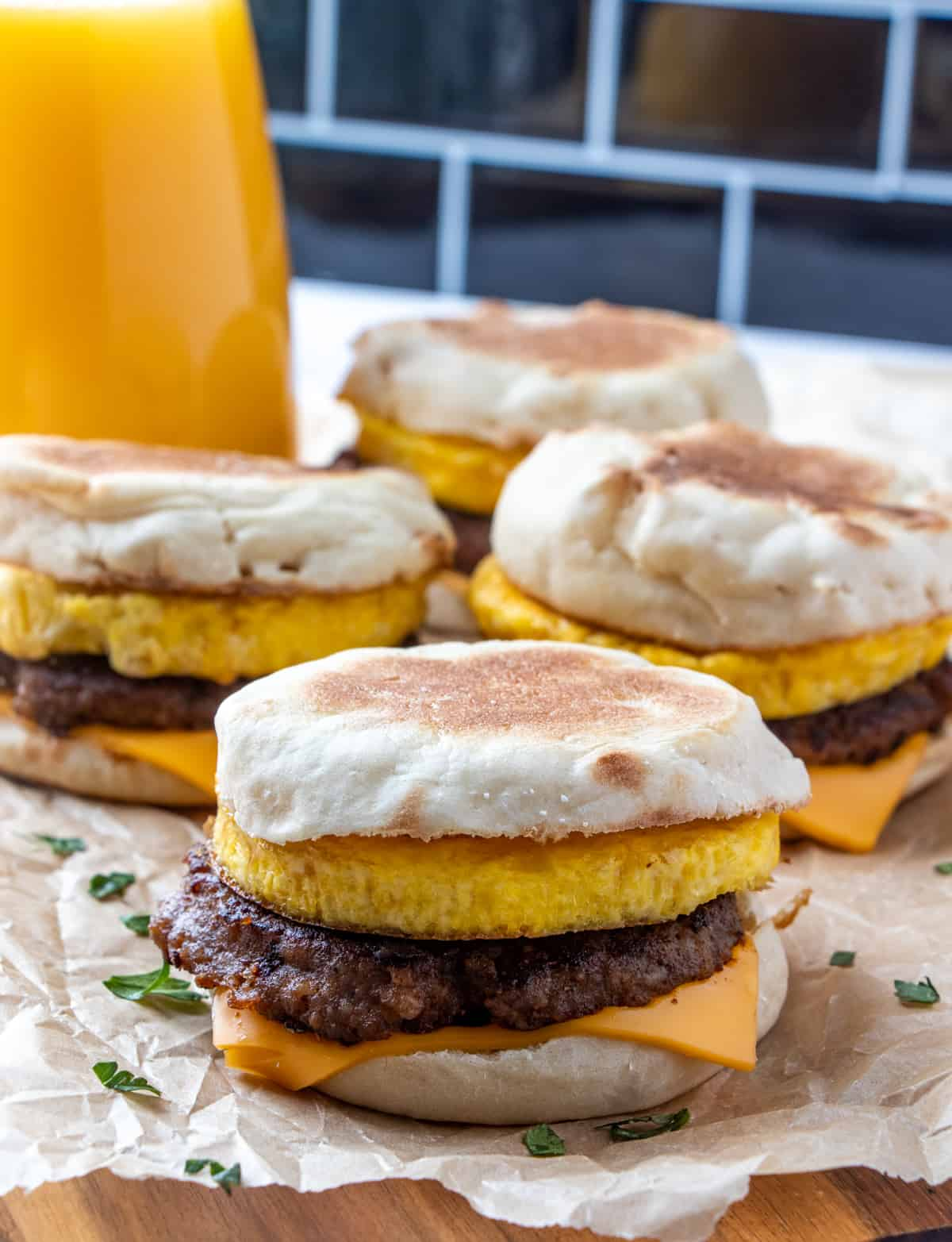 Four sandwiches on parchment paper with orange juice in background