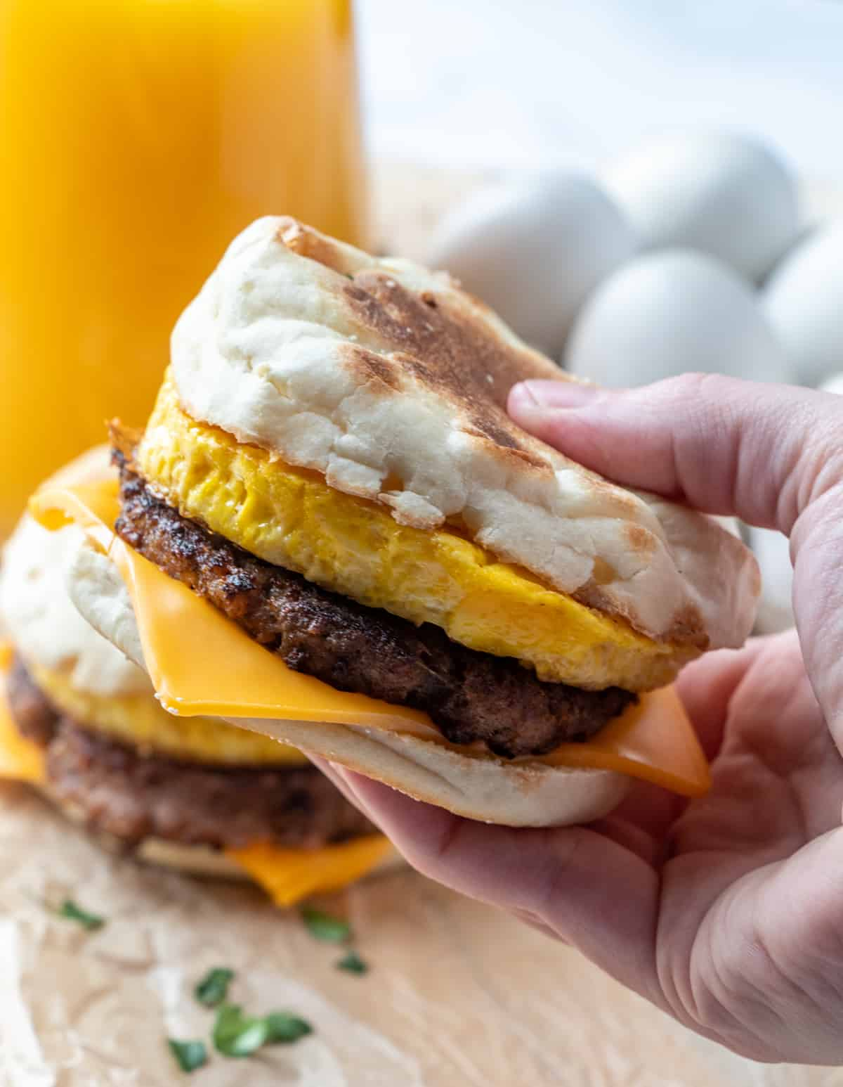 Hand holding one sandwich showing the layers of cheese, sausage and egg