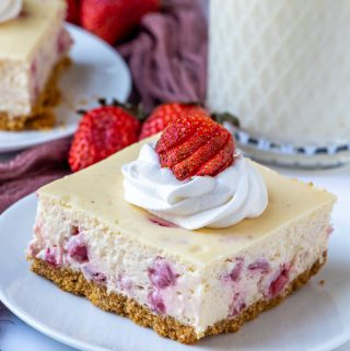 Slice of cheesecake bar on plate with whipped topping and strawberry