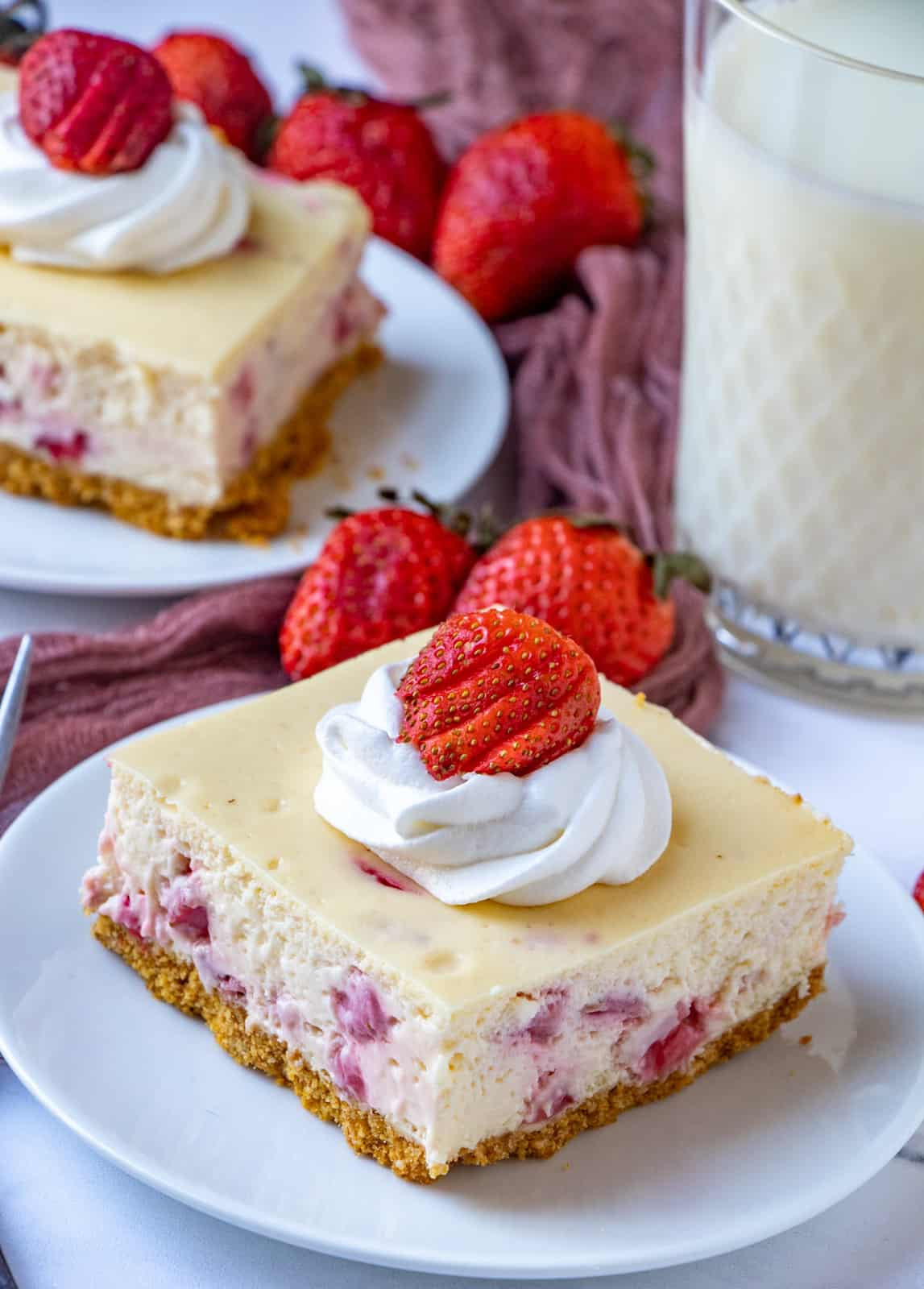 Two white plates with cheesecake bars with whipped cream and strawberries
