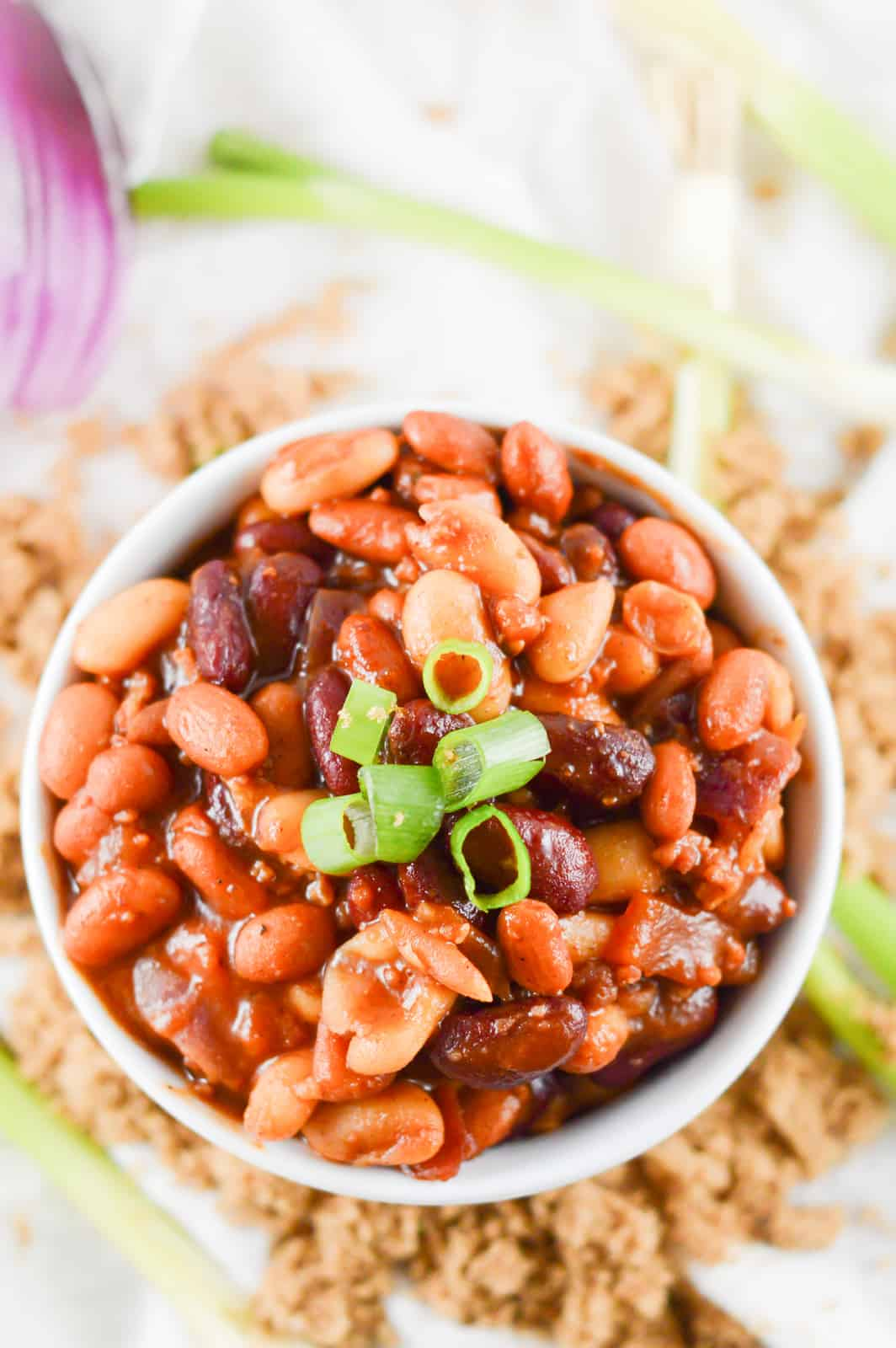 Overhead of homemade baked beans in bowl with brown sugar surrounding bowl