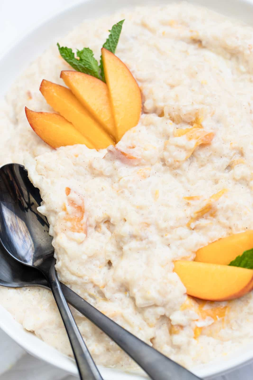 Close up of bowl of Rice Pudding with peaches and spoons in bowl
