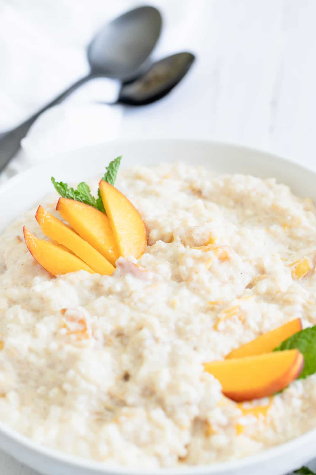Close up of Peach Rice Pudding in bowl garnished with sliced peaches