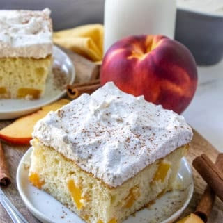 Slice of Peach Cake on white plate sprinkled with ground cinnamon
