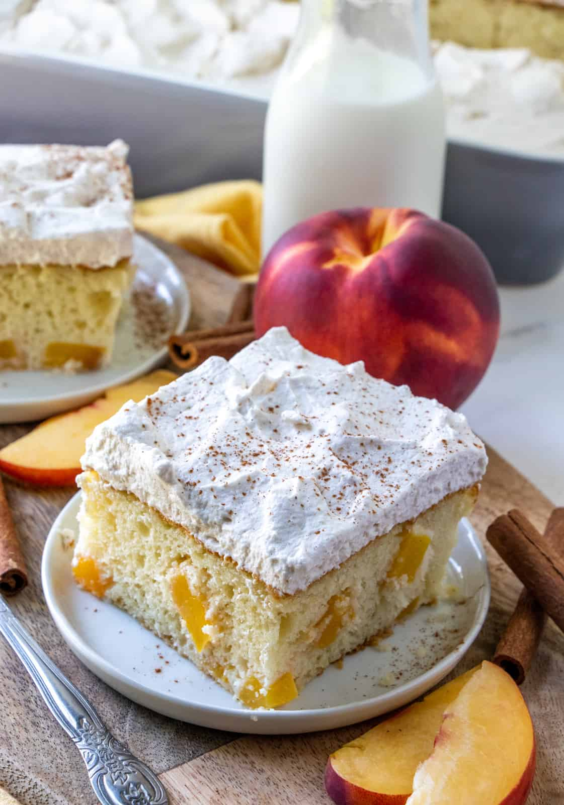 Slice of Peach Cake on white plate sprinkled with ground cinnamon