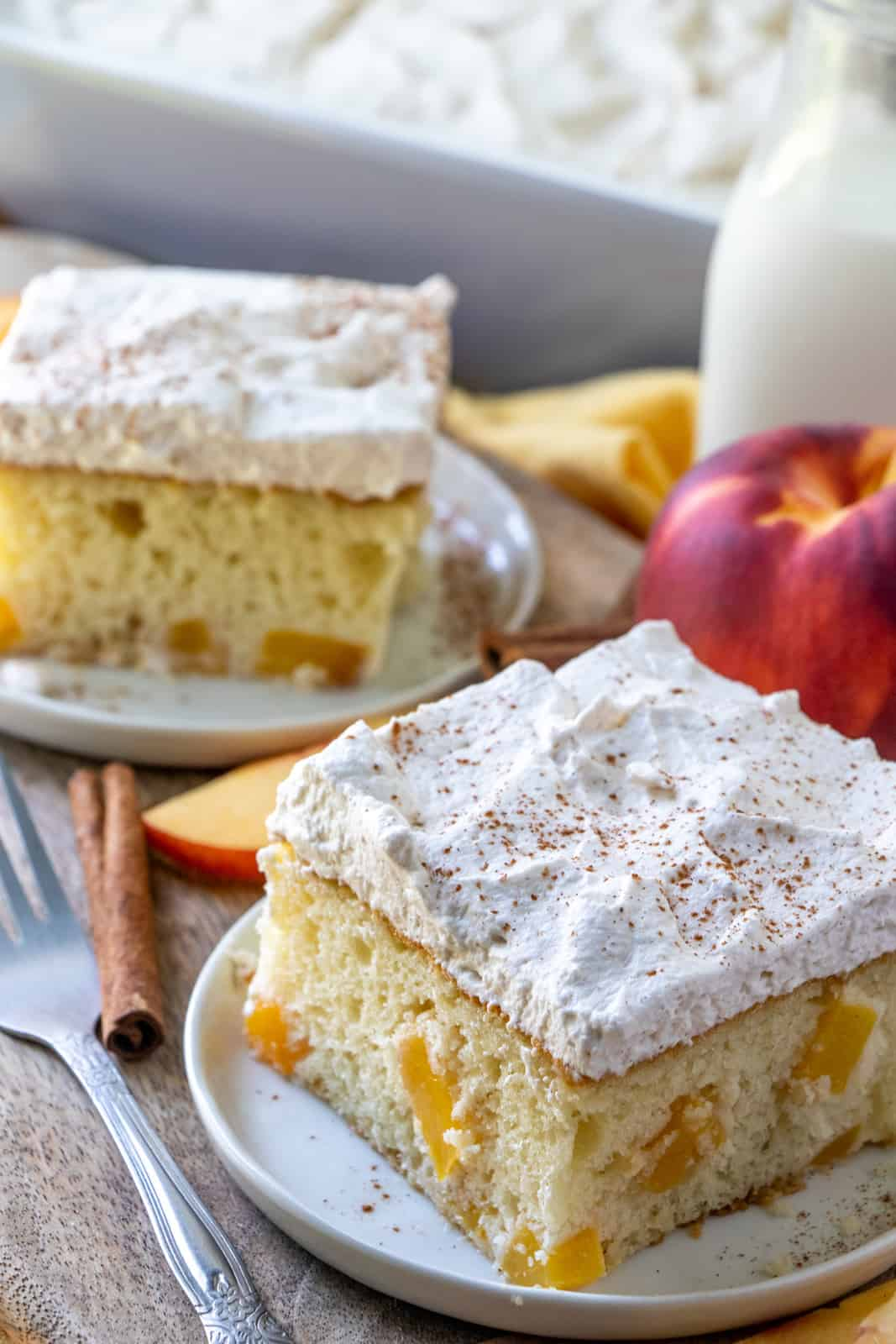 Two slices of cake on white plates with peach and peach slices garnishing around cake