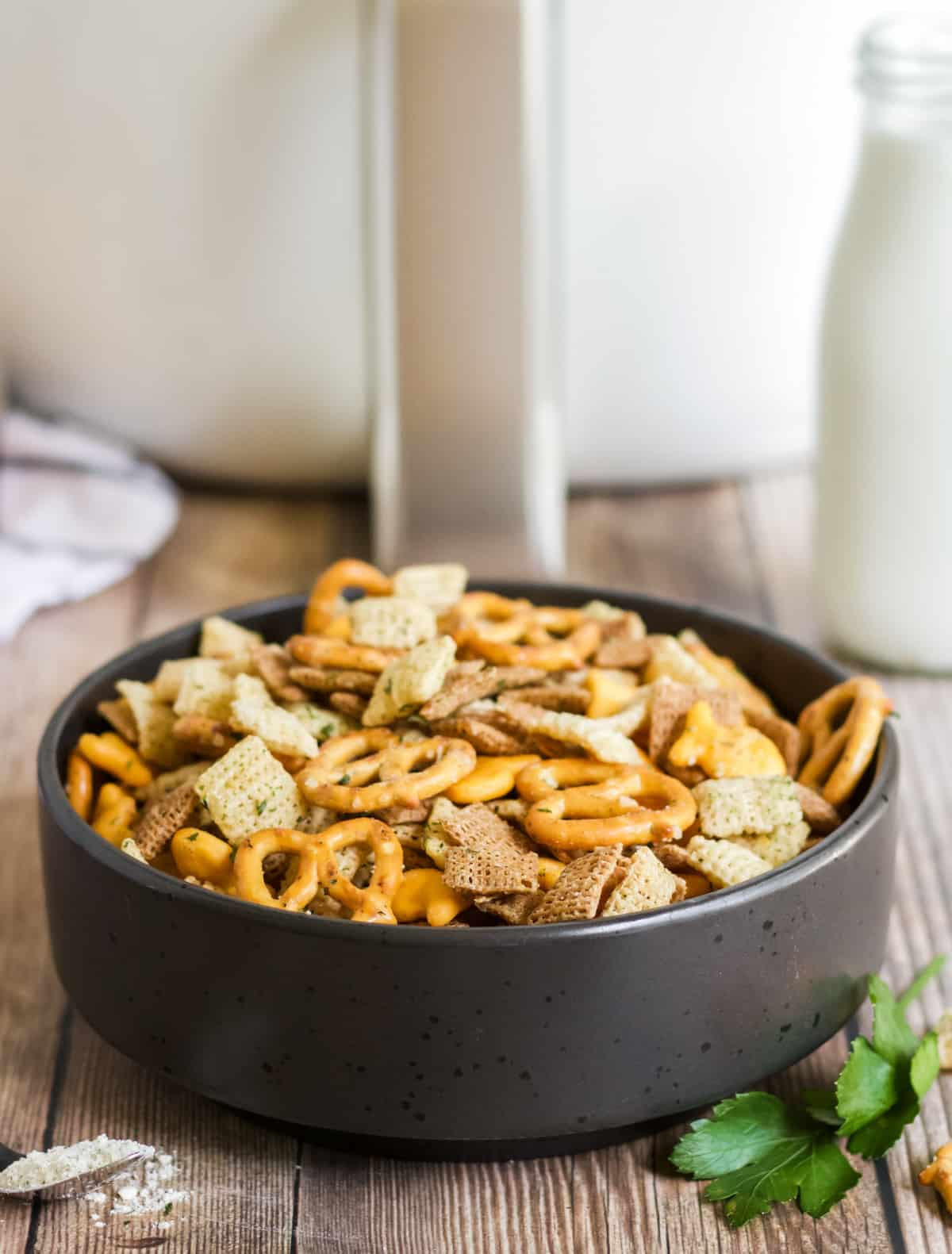 Chex mix in black bowl in front of air fryer