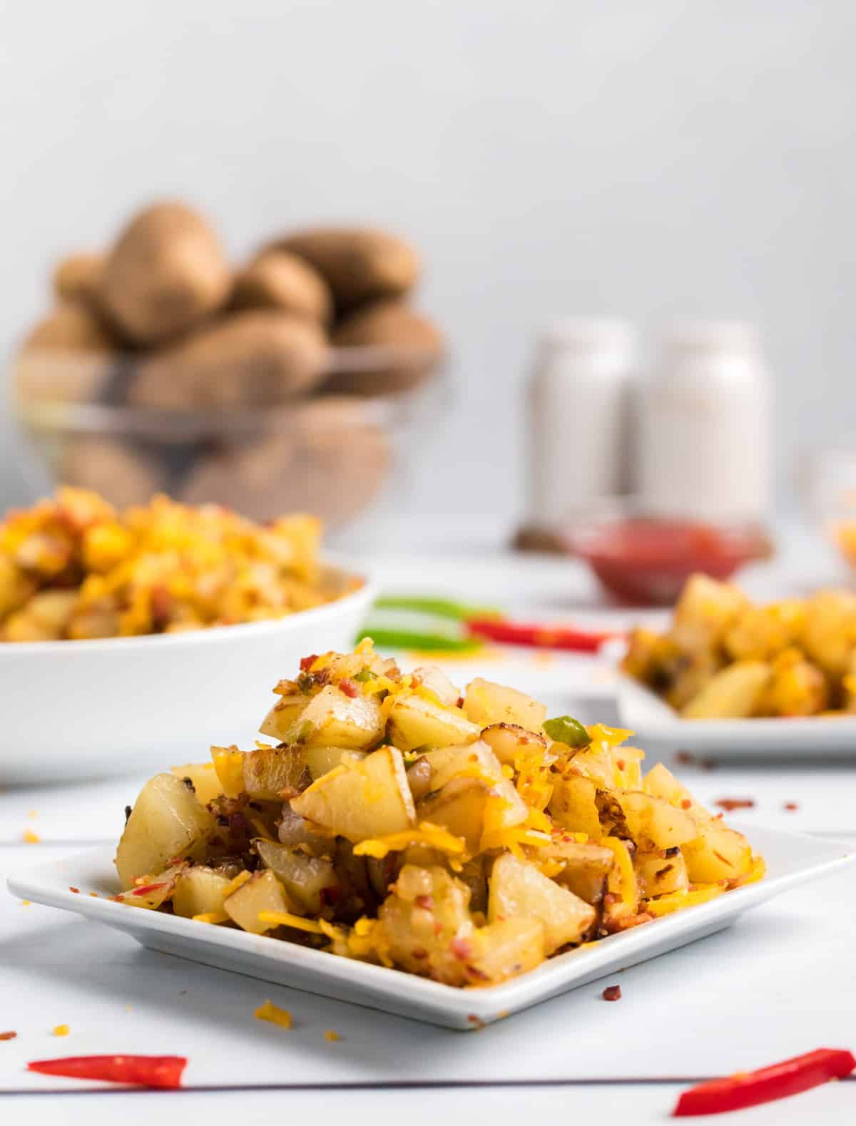 Potatoes on square plate with dish of potatoes in background