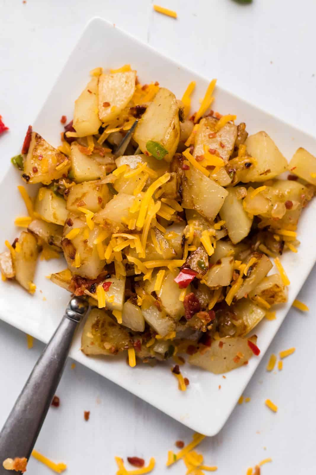 Close up overhead of Cheesy Breakfast Potatoes on white plate with fork