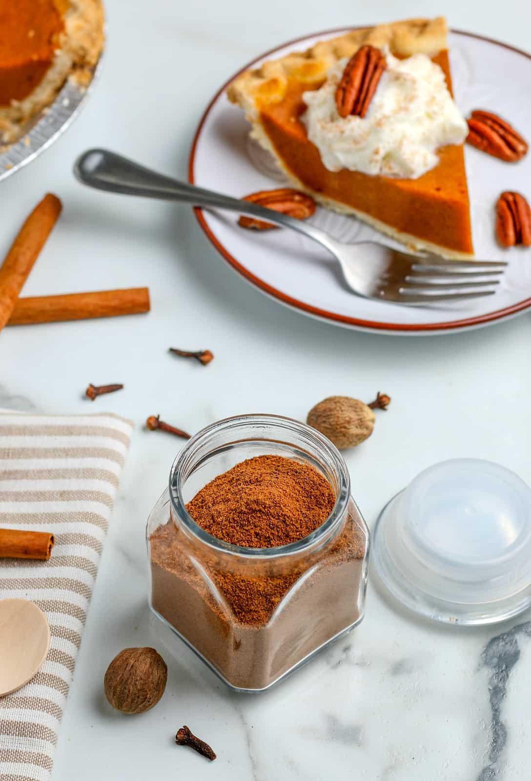 Pumpkin pie spice in container with pie in background