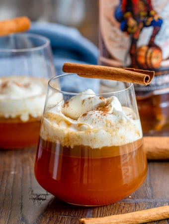 Rum in glass with cinnamon stick on top square image
