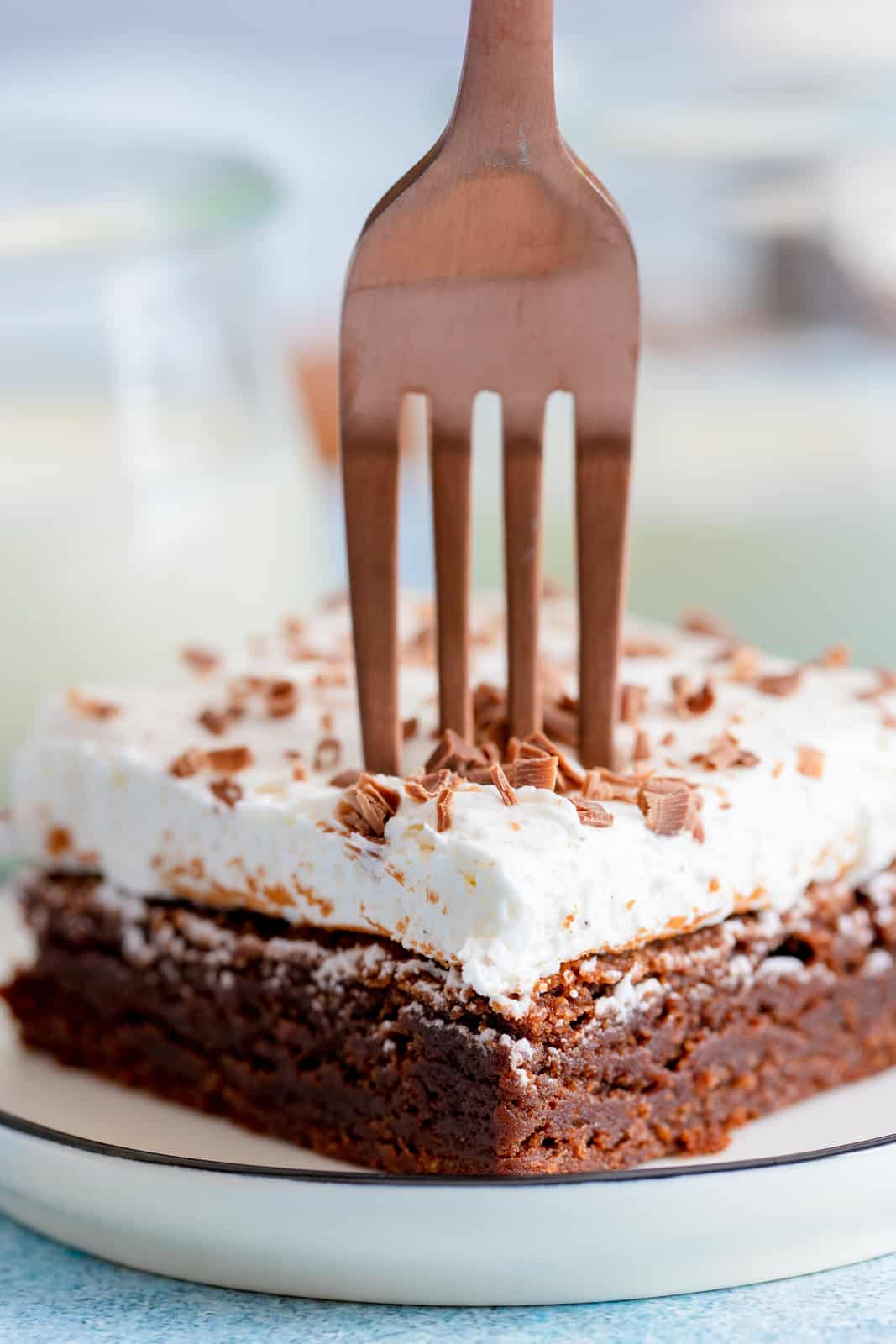 Fork going into top of brownie on white plate