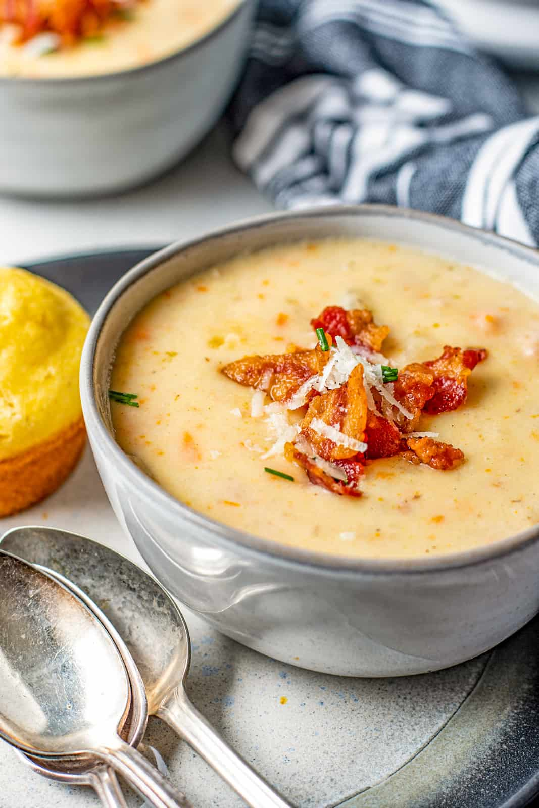 Bowl of soup with bacon and cheese on platter with two spoons