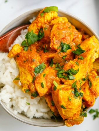 Indian Butter Chicken in bowl with rice and spoon square image