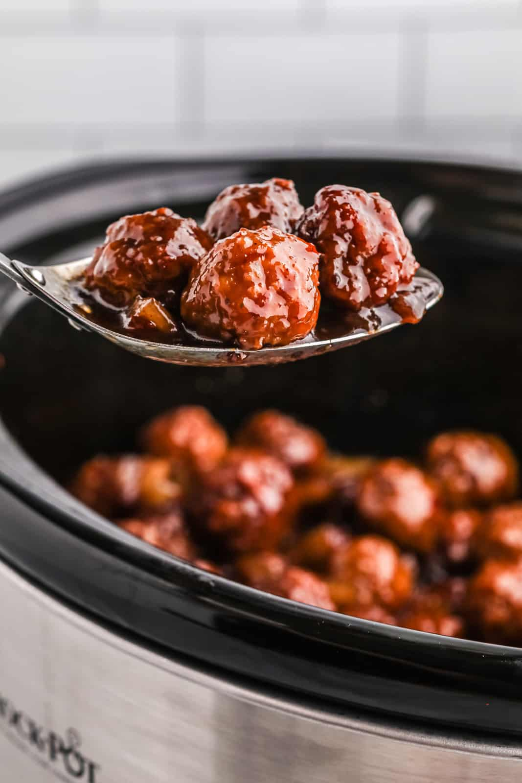Spoon scooping some meatballs out of slow cooker