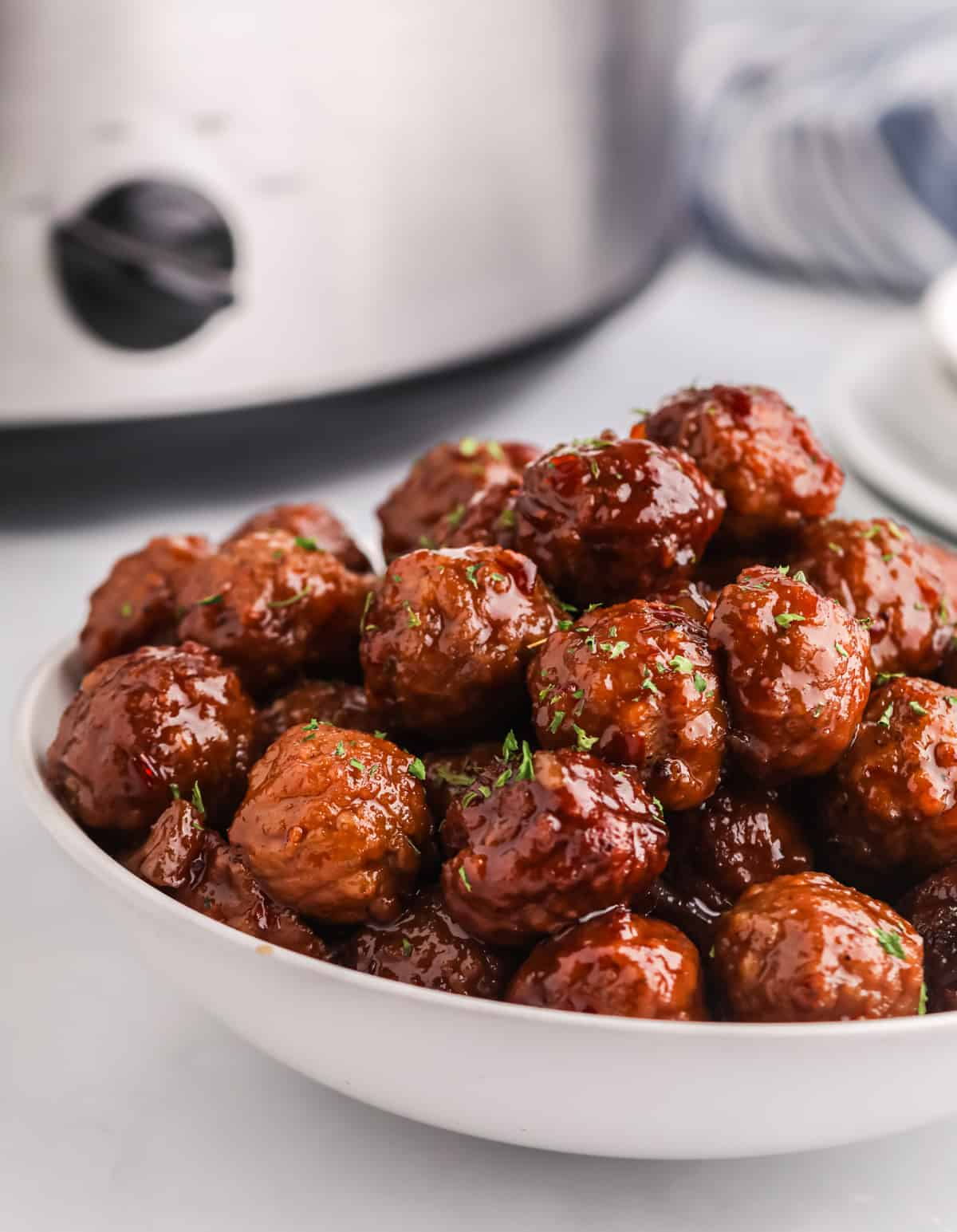 Meatballs stacked in bowl with diced parsley