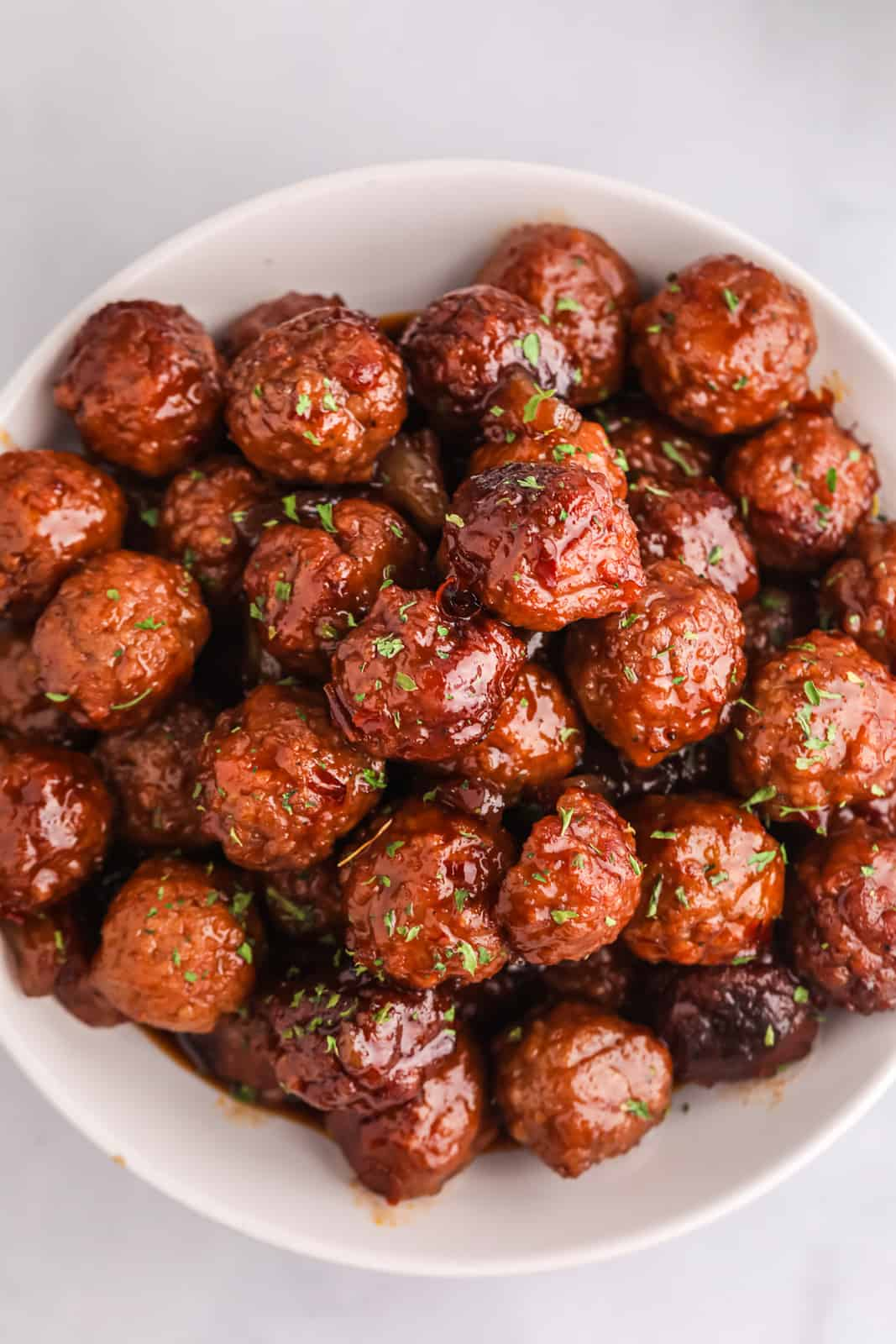 Overhead of meatballs stacked in white bowl with parsley