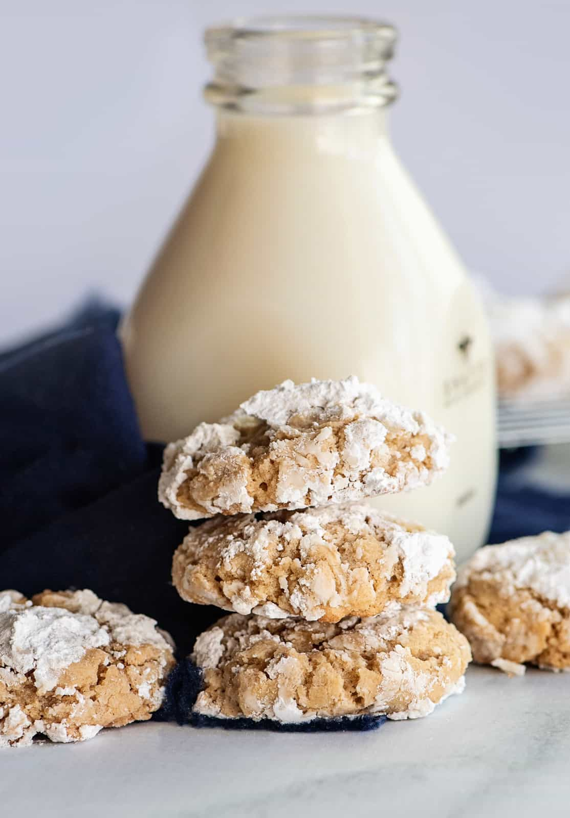 Stacked Crinkle Cookies in front of jug of milk