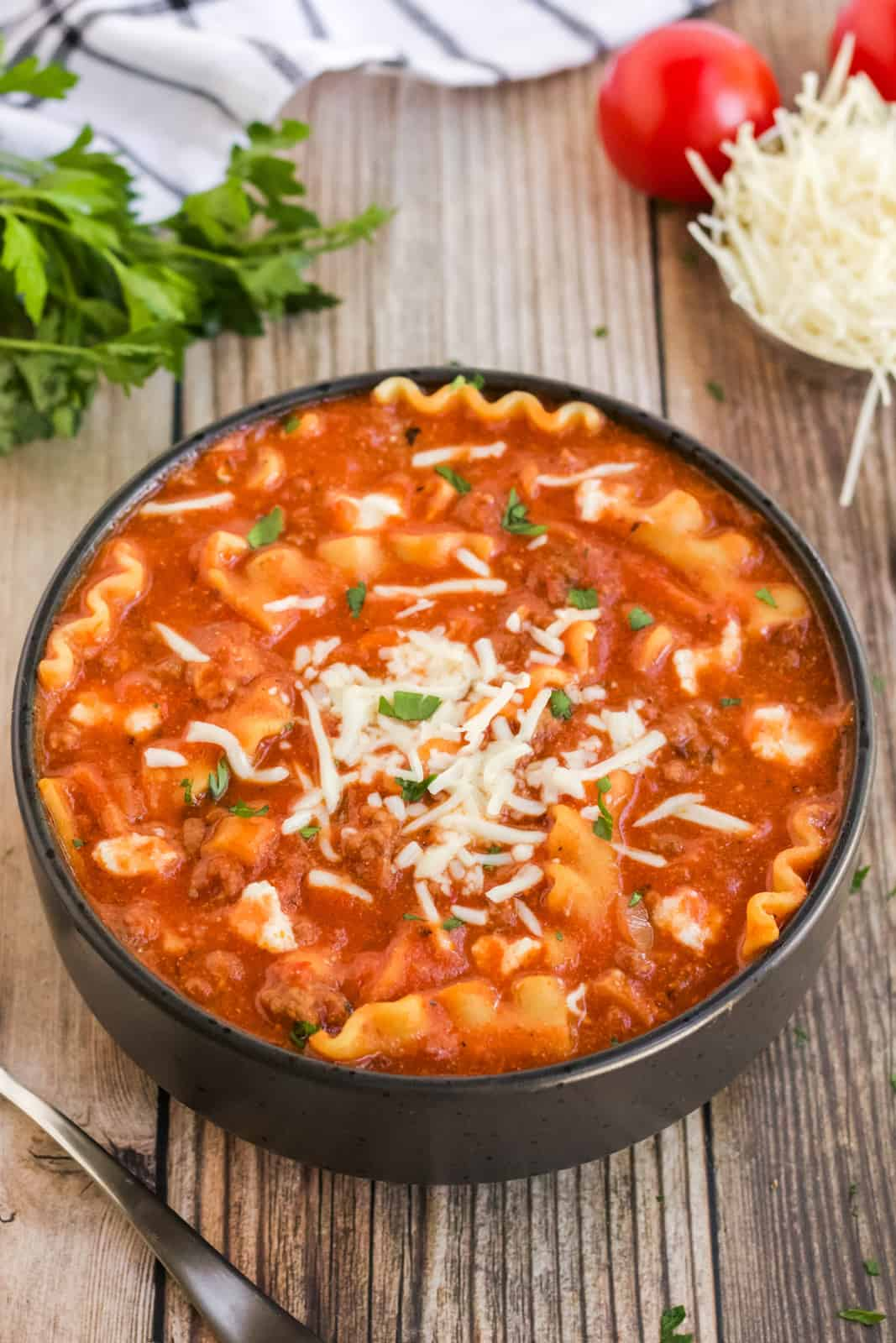 Lasagna Soup in black bowl with cheese