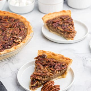 Two slices of Pecan Pie on white plates