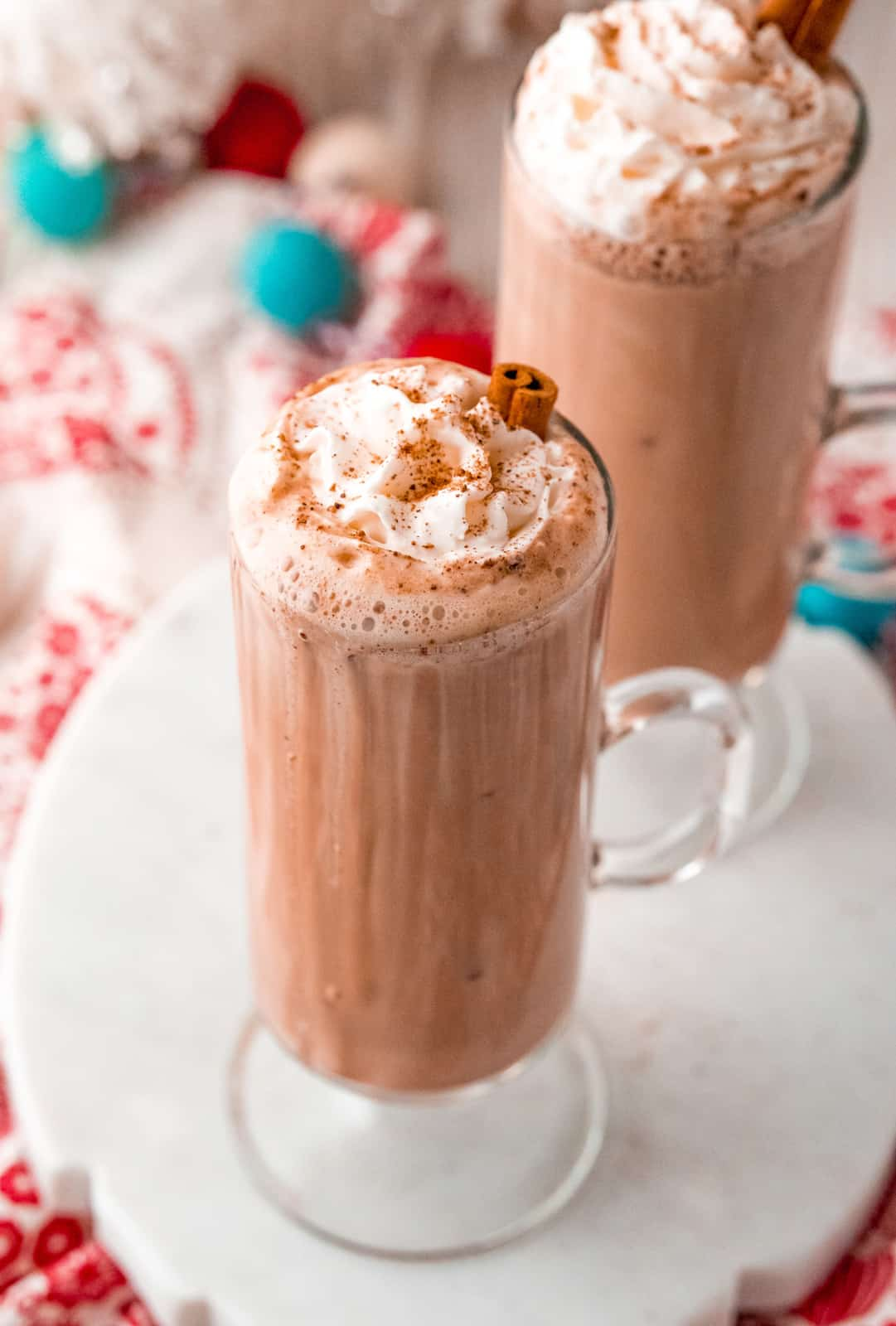 Overhead of two glazes of Eggnog Hot Chocolate topped with whipped cream