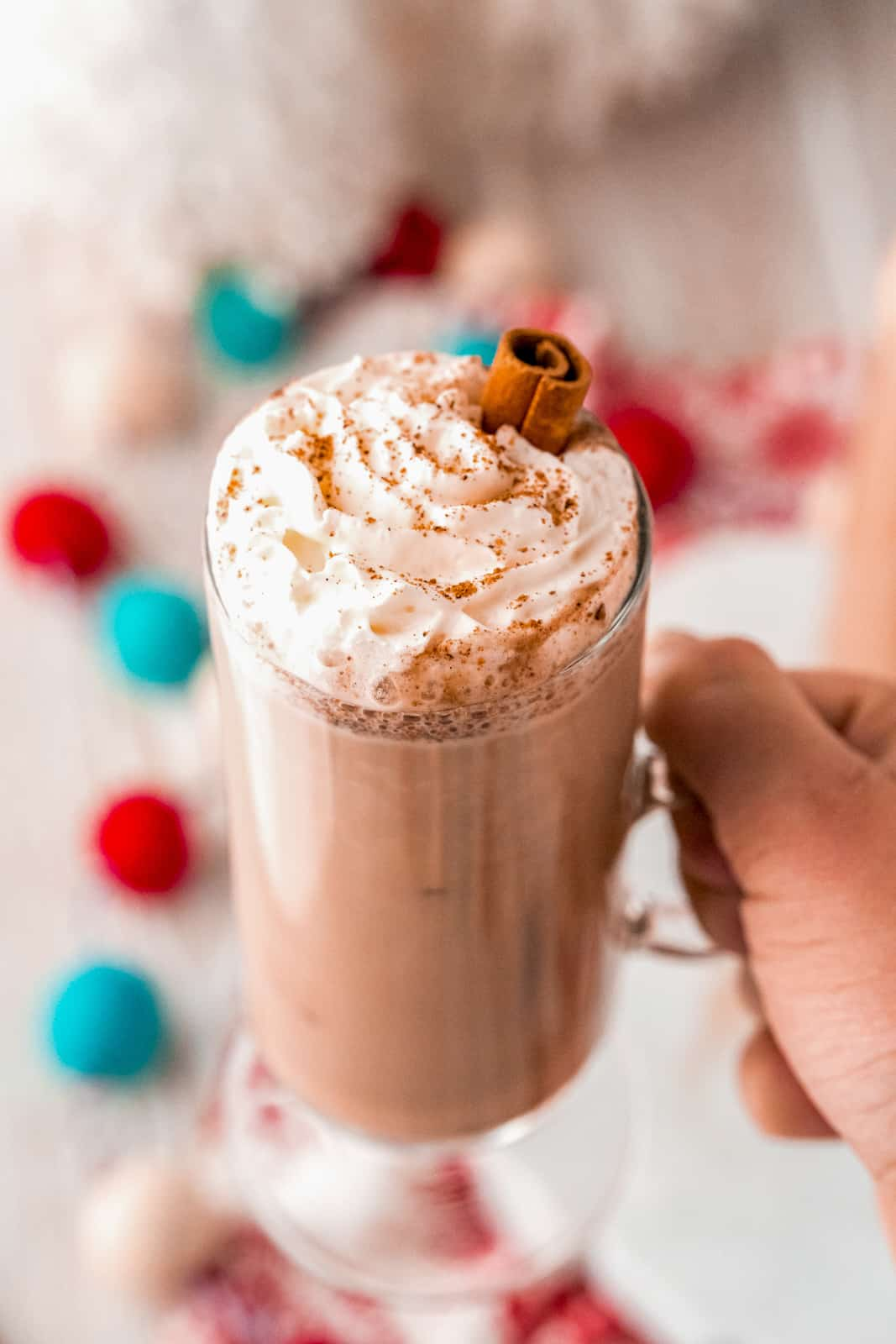 Hand holding up glass of Eggnog Hot Chocolate